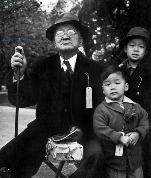 Grandfather and Grandchildren Awaiting Evacuation Bus, Hayward, California, May 8th 1942 (b/w photo)