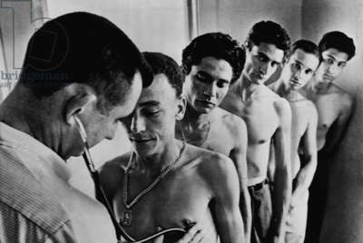 Recruits for the Bay of Pigs invasion. The CIA opened recruiting offices in Miami where refugees volunteered to fight against Castro. This photo shows a group of recruits at one center as they received their physical. Aug. 1960-April 1961