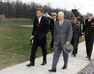 President Kennedy and former President Eisenhower walk ahead of military aides at Camp David. The group met to discuss foreign relations with Cuba after the disastrous Bay of Pigs invasion. April 22, 1961