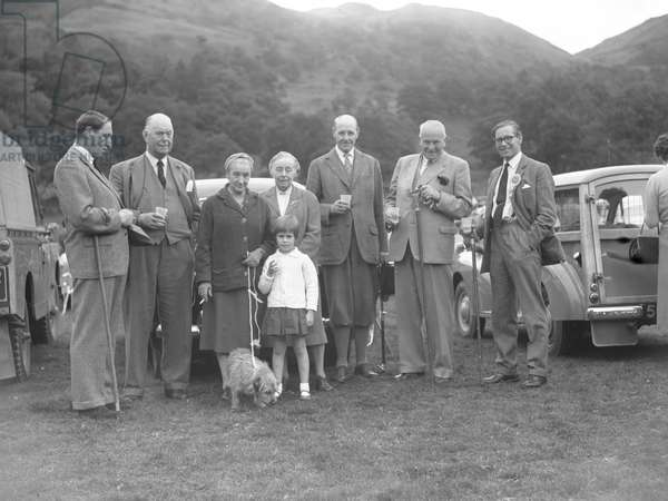 A portrait of a group of men and women smartly dressed (and a child and a dog) stood infront of cars, 1930s-60s (b/w photo)