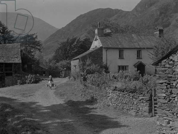A view of a woman carrying two buckets walking down a track at Yewtree Farm near Coniston, 1930s-60s (b/w photo)