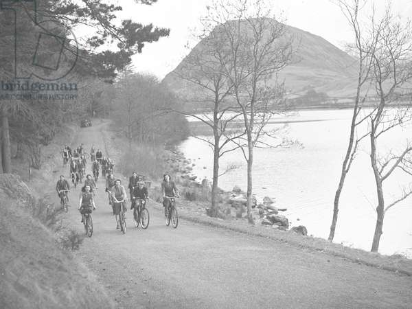 A view of a group of cyclists pedalling along a road at the side of a lake, fells in the background, 1930s-60s (b/w photo)