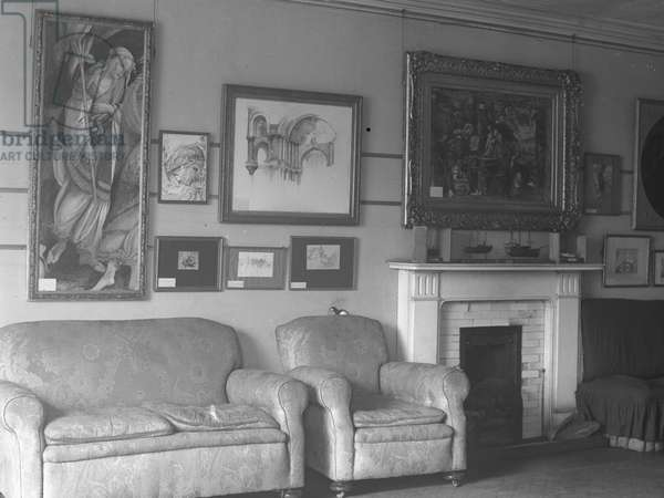 A room at Brantwood, possibly a sitting room, with artwork on the walls, fireplace and sea; seascape;ting, 1930s-60s (b/w photo)