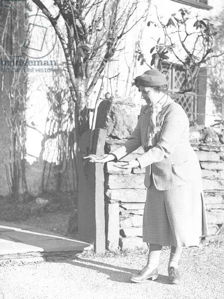 A view of a woman standing in front of Dove Cottage feeding birds from her hands, 1930s-60s (b/w photo)