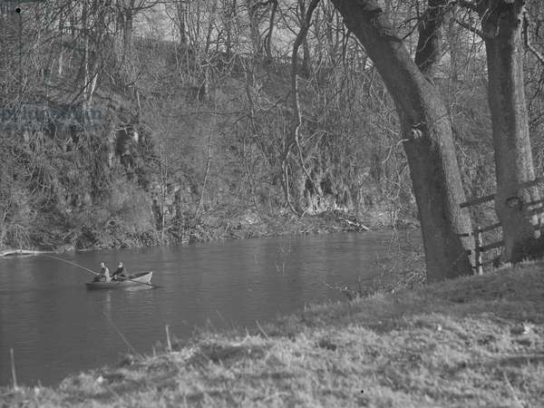 Two men in a rowing boat on a river fishing, 1930s-60s (b/w photo)