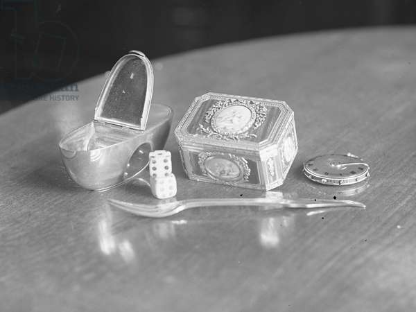 A collection of objects including dice, decorative containers, a fork and a watch mechanism, 1930s-60s (b/w photo)