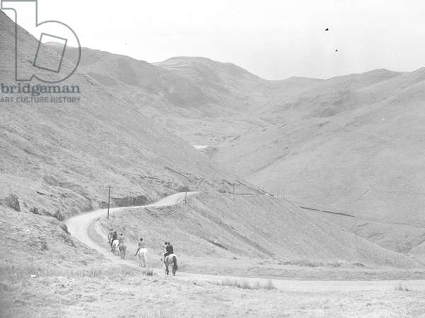 A view of a group of people pony trekking along a path through fells, 1930s-60s (b/w photo)