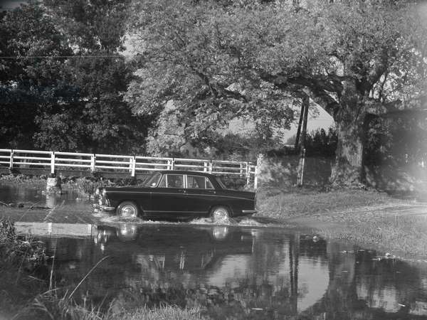 Car driving through ford at Orton from right to left of image, 1930s-60s (b/w photo)