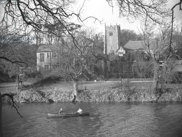 A view of some people in a rowing boat on the River Lune possibly fishing, in the background are buildings and a church; architecture; religious; ecclesiastical;, 1930s-60s (b/w photo)