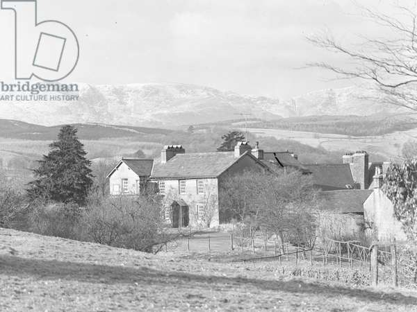 A view looking towards the front façade of Hill Top Farm, the home of Beatrix Potter, with snow covered fells in the background, 1930s-60s (b/w photo)