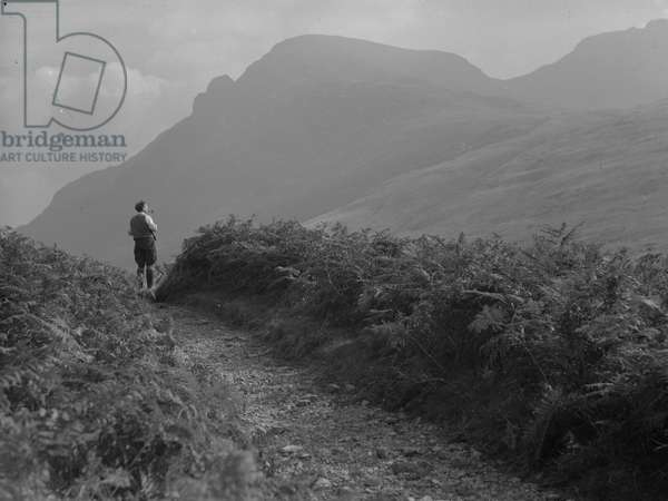 A view of a man standing on a path looking out across fells, 1930s-60s (b/w photo)