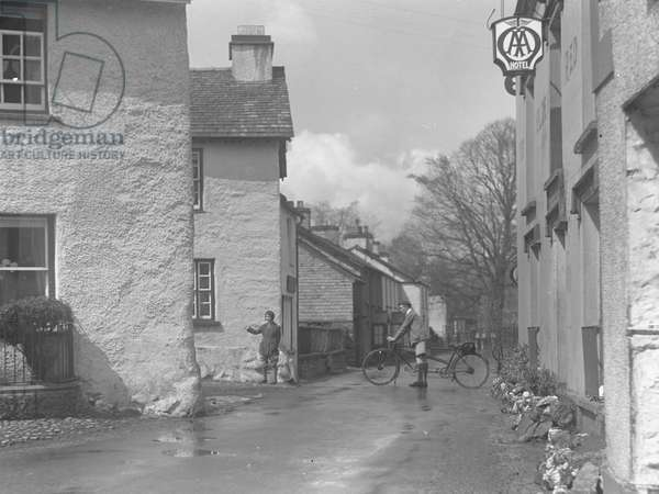 Two people with tandem bicycle in the street at Hawkshead with AA Hotel sign in foreground, 1930s-60s (b/w photo)