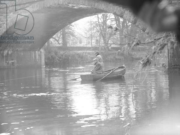 Two men in a rowing boat underneath a bridge on a river fishing, 1930s-60s (b/w photo)