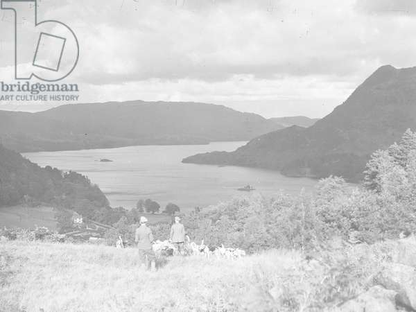 Two men and hunting hounds stand on a hillside looking out across a lake and fells, 1930s-60s (b/w photo)