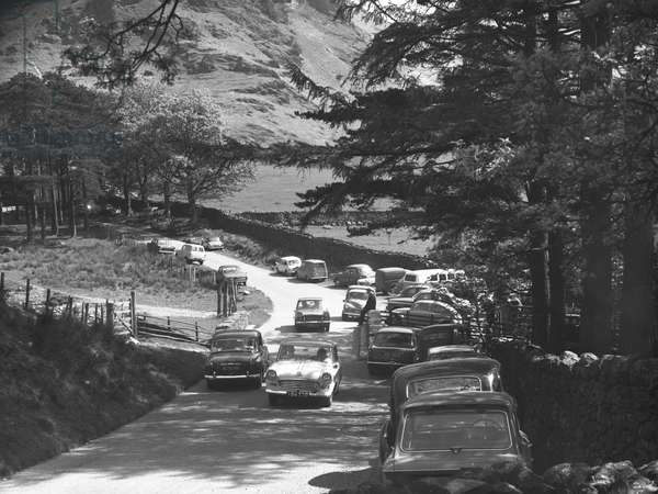 Cars on narrow road at Buttermere with Triumph Heral, Mg Midget and VW Beetle, 1930s-60s (b/w photo)