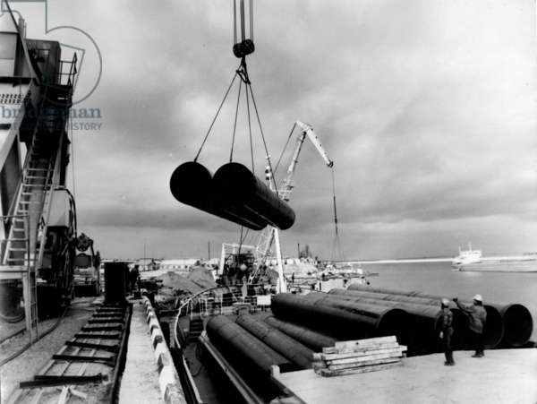 Pipes being unloaded from the river barge, 1977 (b/w photo)