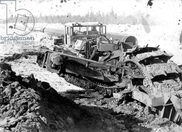 A dredge preparing the ground for pipes, 1977 (b/w photo)