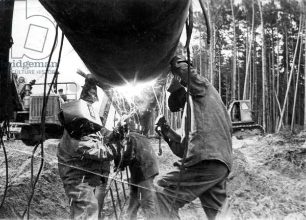 Welding the pipes, 1977 (b/w photo)