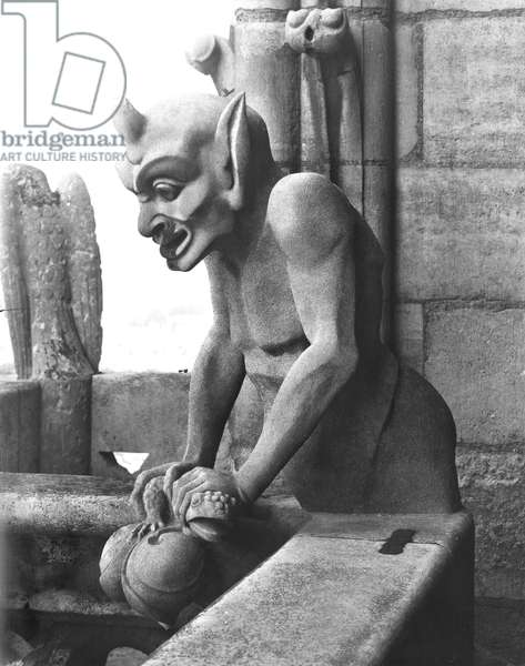 Gargoyle from the balustrade of the Grande Galerie, devil holding a toad, replica of a 12th century original (stone) (b/w photo)