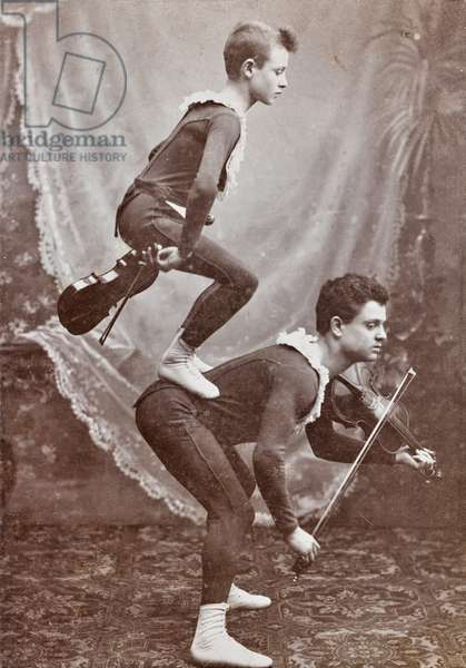 Young acrobats during a performance with violins
