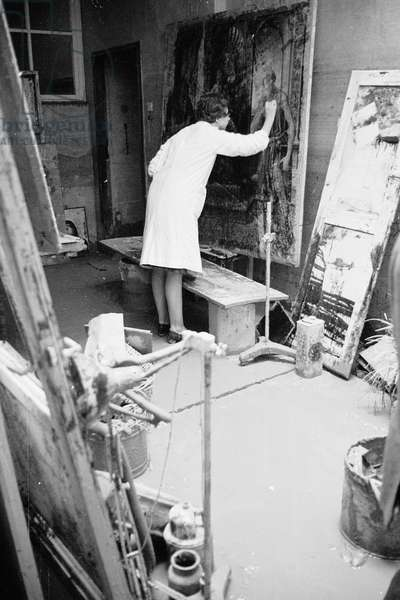 Restorer working on a painting damaged by the flood of florence, November 1966 (b/w photo)