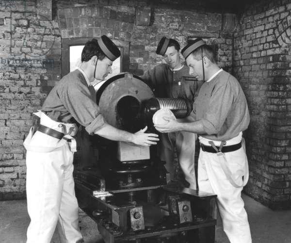Men loading a 32 pounder Monk Pattern SBBL gun from 1883 (b/w photo)