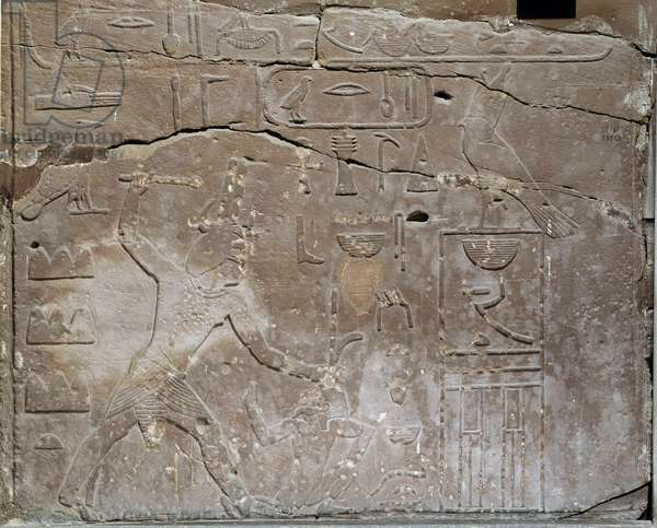 Egyptian antiquite: fragment of decoration in limestone depicting a man striking his enemy. Museum of Egypt, Cairo.