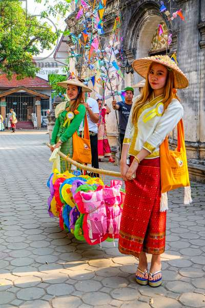 Fashionable Shan girls carry offerings at the Poy Sang Long (Shan ordination ceremony for boys aged 7-14) parade; Wat Pa Pao, Chiang Mai, Thailand.
