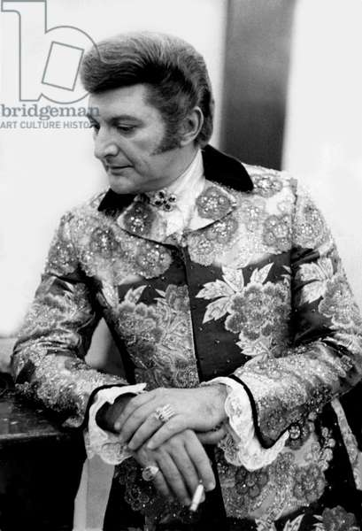 Liberace smoking in a London rehearsal room, 1968 (b/w photo)