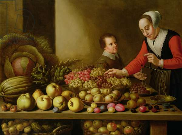 Girl selling grapes from a large table laden with fruit and vegetables