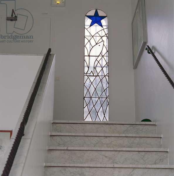 Entrance stairs to the Chapel of the Rosary with stained glass window depicting a fish caught in a net beneath the Star of Salvation, 1948-51 (stained glass)