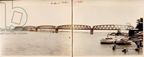 Bridge over Indus at Kotri. Panoramic view of the girder railway bridge, composed of two prints, with river steamers and other craft moored at the bank on the right. A group of men fishing for palla can be seen in the right foreground.