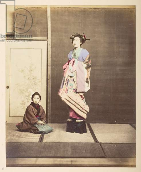[?Geisha, ] Full-length standing studio portrait of a young woman in elevated shoes, her young attendant kneeling on the floor beside her,  Photographer: UnknownLucas Collection: Photographic record of the world tour of Charles James and Morton P,  Lucas, 1877-79,  Dimensions: 242 mm x 194 mm