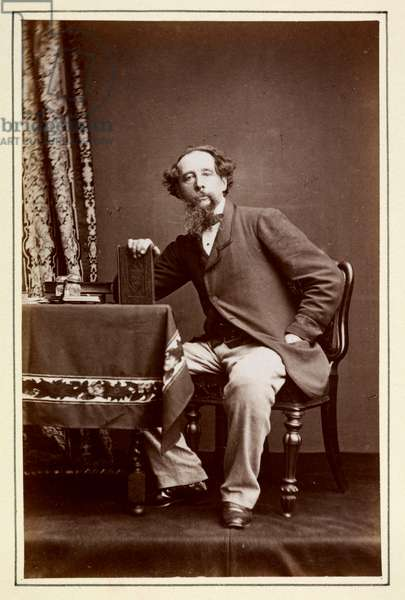 Charles Dickens seated at a table.