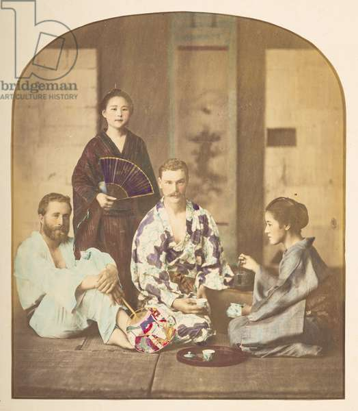 Portrait of Charles James Lucas, Japan, Portrait of Charles James Lucas (1853-1928), the compiler of this album, wearing Japanese dress and attended by two Japanese women performng the formalities of the tea ceremony,  An unidentified European companion (probably his brother Morton Lucas) is seated to the left, Photographer: Unknown Lucas Collection: Photographic record of the world tour of Charles James and Morton P,  Lucas, 1877-79,  1878Dimensions: 188 mm x 244 mm