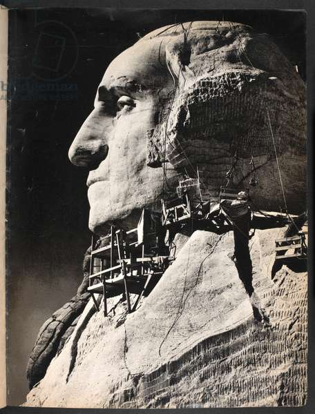 View of Mount Rushmore National memorial, of the rock sculpture of the face of President George Washington, showing scaffolding.