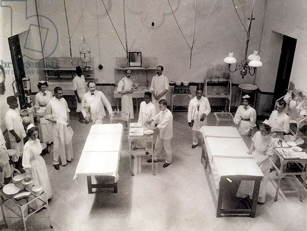 Staff preparing for an operation in the theatre at Jamsetjee Jejebhoy Hospital, Bombay, 1900s (b/w photo)