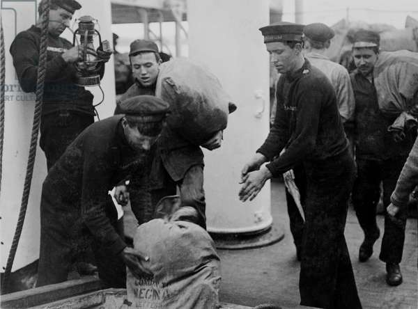 Crewmen loading mail and adjusting a Liner's lamp (b/w photo)