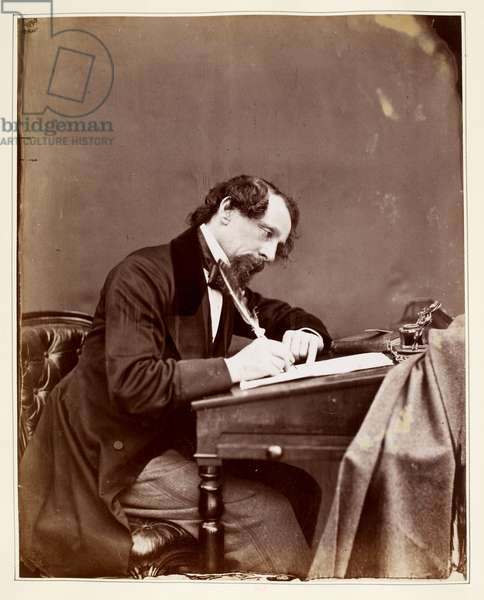 Charles Dickens sitting at his writing desk.