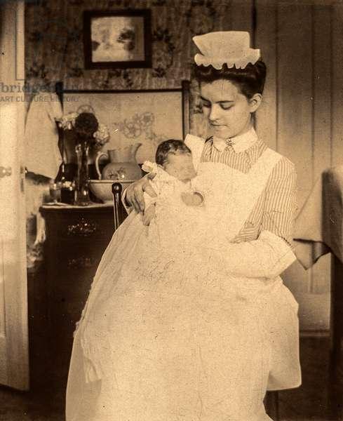 Portrait of Nurse Holding Newborn Baby (silver gelatin print)