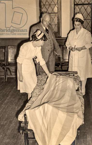 Red Cross Nurses Examine Patient on Cot, c.1940s-1950s (silver gelatin print)