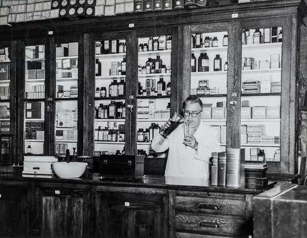 Pharmacist Fills Beaker in Sing Sing Prison's Pharmacy, Sing Sing Prison Hospital Pharmacy, New York, USA, c.1920 (silver gelatin print)