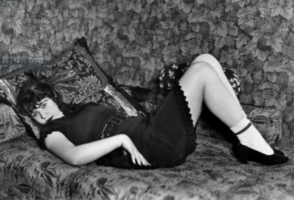 Young prostitute laid on a sofa in a provocative pose, 30's - 40's