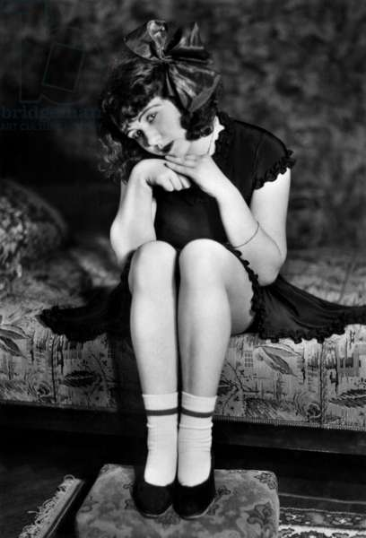 Young prostitute seated on a sofa in a sober pose, 30's - 40's