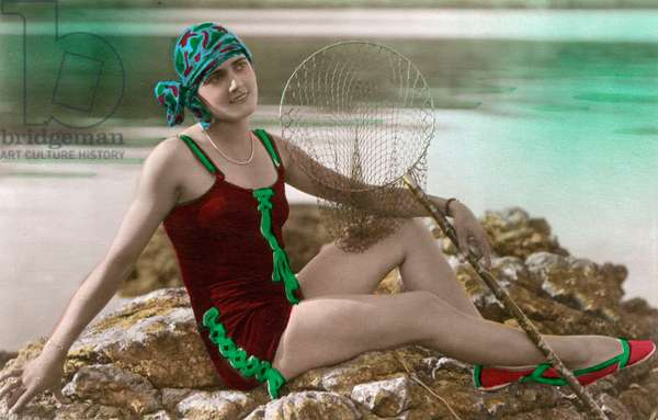 A young woman with a landing net posing on a rock, postcard, c. 1920