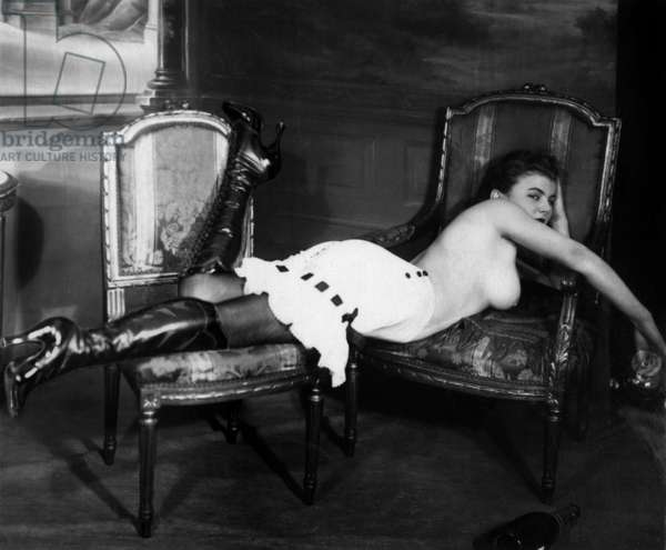 Prostitute half naked posing laid on two chairs, 1930s (b/w photo)
