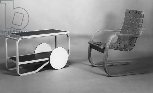 (LtoR) Tea Trolley, model No.98, manufactured by Aztek, 1936, and a Cantilevered Armchair '406', 1933, designed by Alvar Aalto (1898-1976) (b/w photo) (wood and leather)