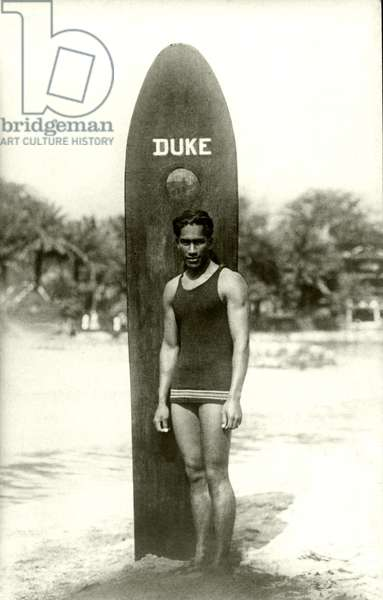 Duke Kahanamoku with his surfboard, c.1920s (b/w photo)