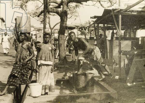 Collecting water from a hand pump, Accra, 1951-52 (b/w photo) [1995/076/5/2/2/49]