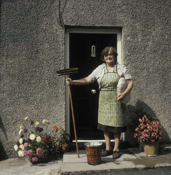 A woman stands on her front doorstep, broom in hand and kneeling cushion under her arm, a bucket of water at her feet, after cleaning her doorstep, Laugharne, Carmarthenshire, Wales (photo)
